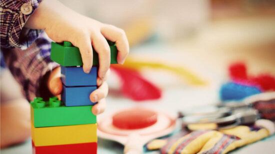 eine Kinderhand baut einen Turm aus bunten Plastikbauklötzen