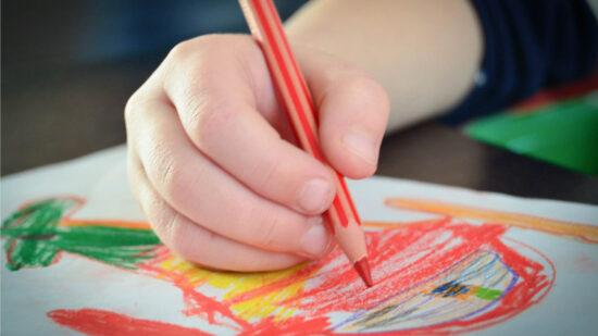 Eine Kinderhand malt ein buntes Bild