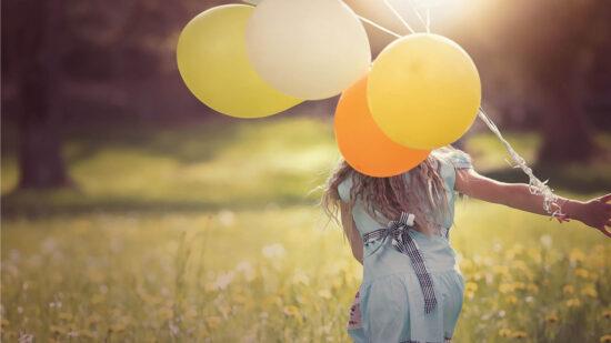 Ein Kind rennt mit Luftballons über eine Blumenwiese